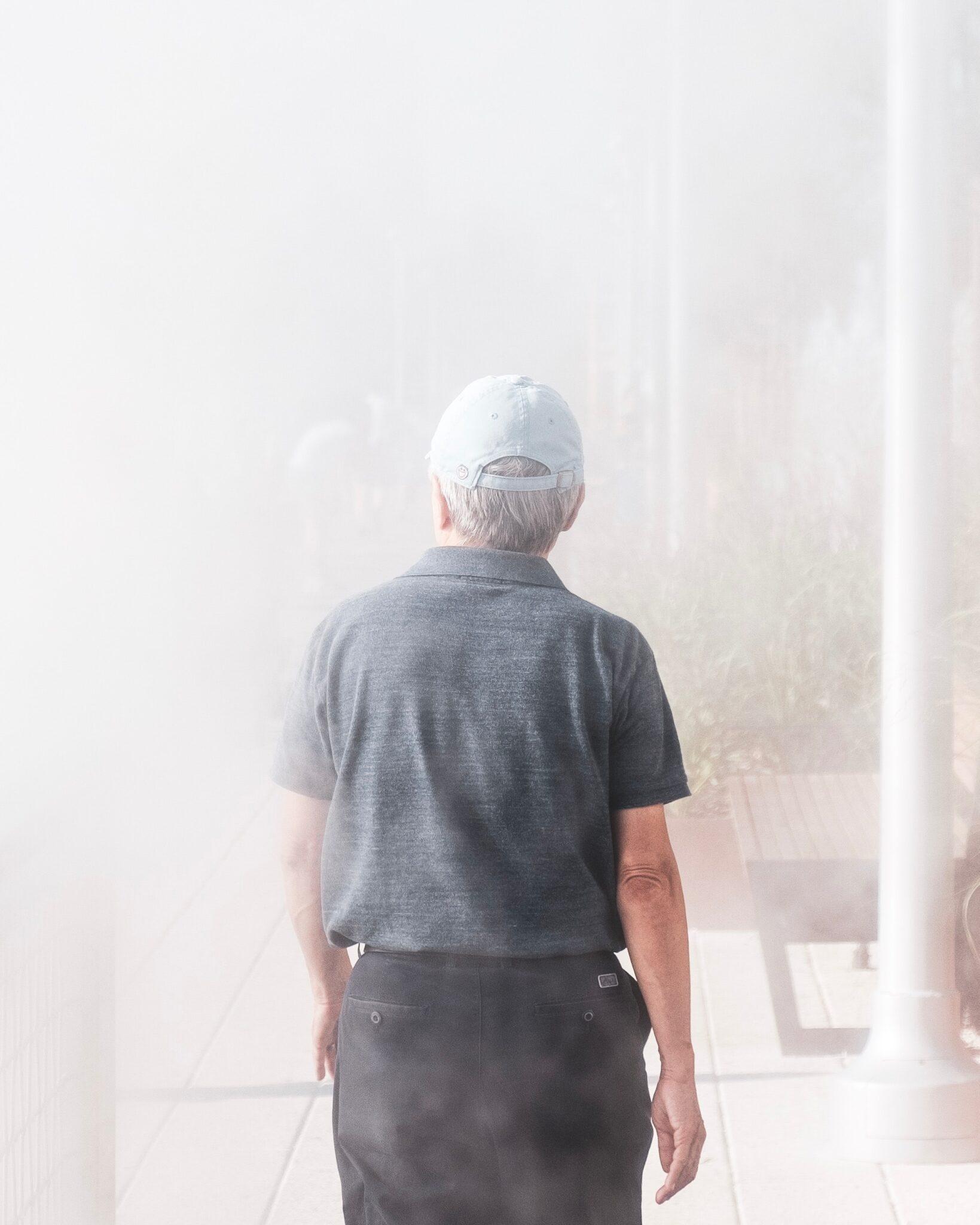 missing man, man in cap walking toward haze