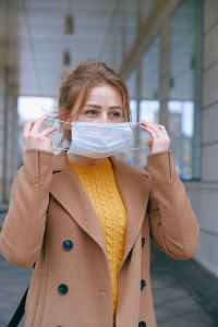 woman in yellow sweater donning face mask
