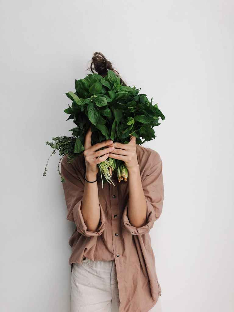 herb garden, woman covering face with bouquet of herbs