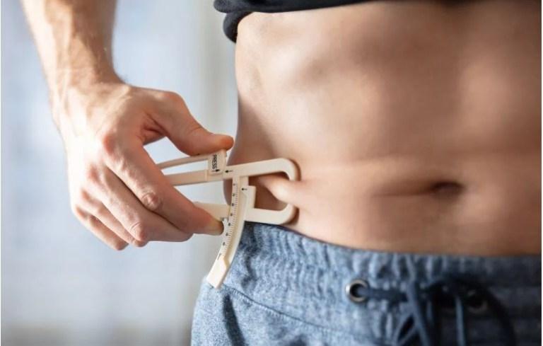 Visceral fat, man measuring subcutaneous fat