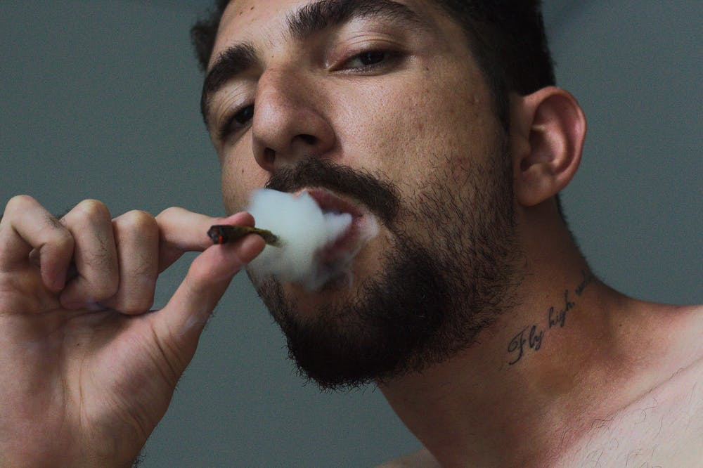 CBD, man blowing puff of smoke from a joint