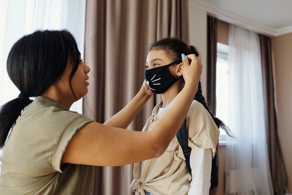 Woman placing face mask on girl's face