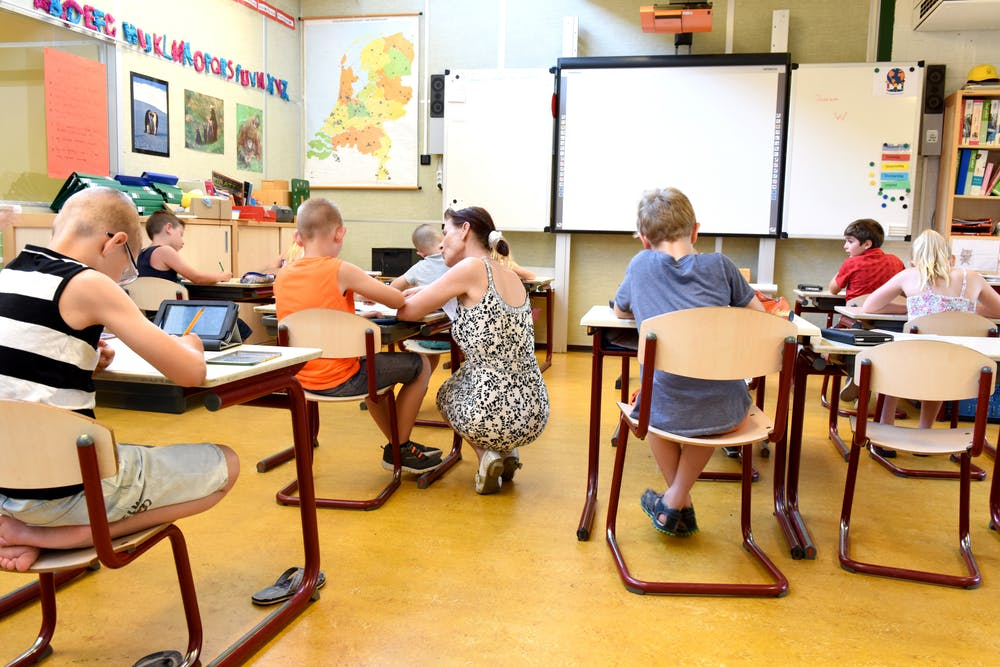 re-opening schools, teacher stooping by student's desk in class