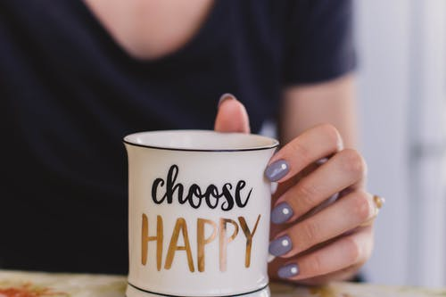 hand with purple nails holding choose happy mug