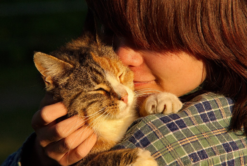 Woman snuggling up to cat