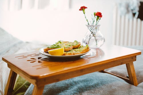 tray sitting on bed with breakfast and vase of flowers on it