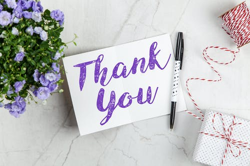 thank you written in purple ink on white card with pen and bouquet of flowers nearby