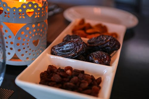 white serving dish filled with raisins and dates