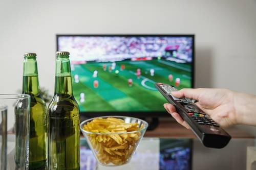 money wasters, two beers, bowl of chips, tv and hand holding remote
