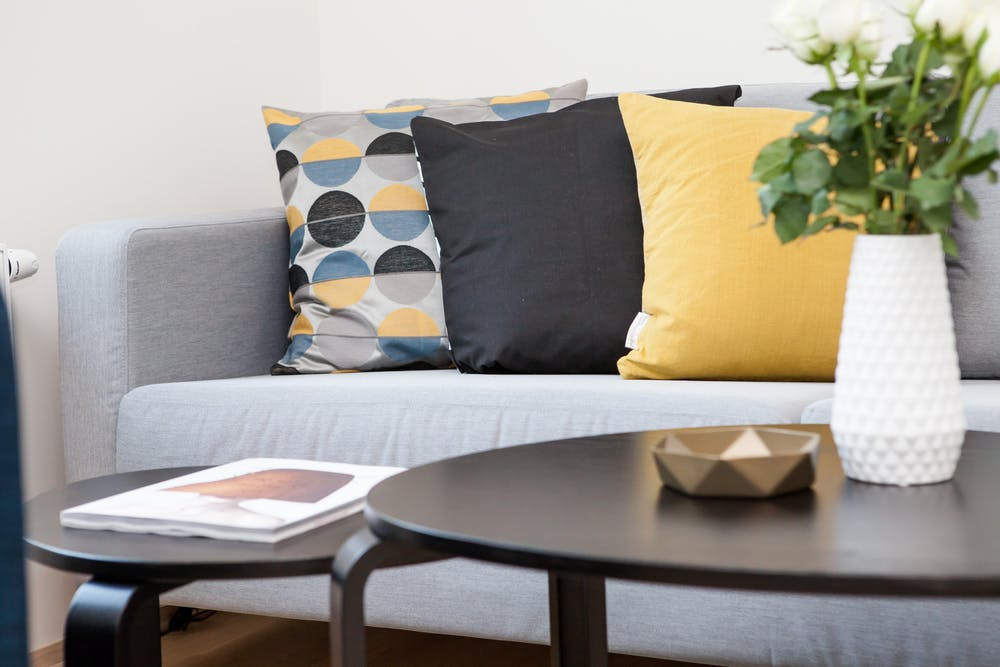 yellow, gray and patterned accent pillows on sofa near coffee table