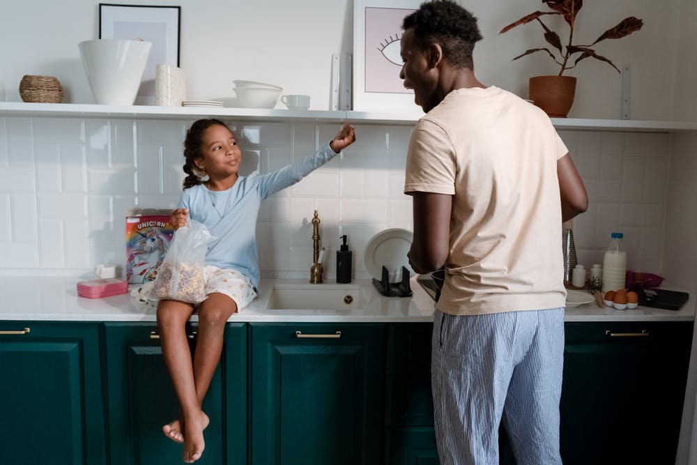 home interior, man in white tee shirt standing near girl sitting on countertop, green cabinets
