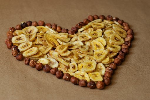 healthy snacks, heart made of nuts and sliced bananas