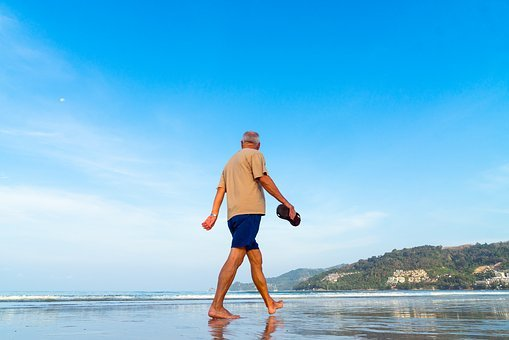 inner peace, older man walking barefoot on the beach