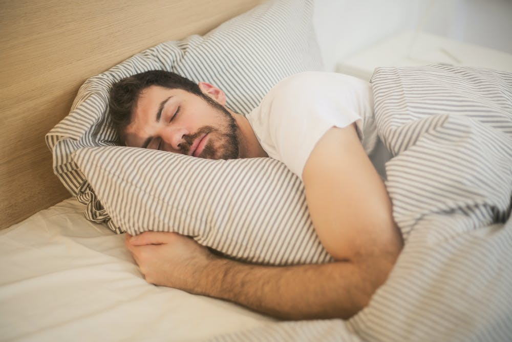 man with brown hair and beard sleeping, white tee shirt