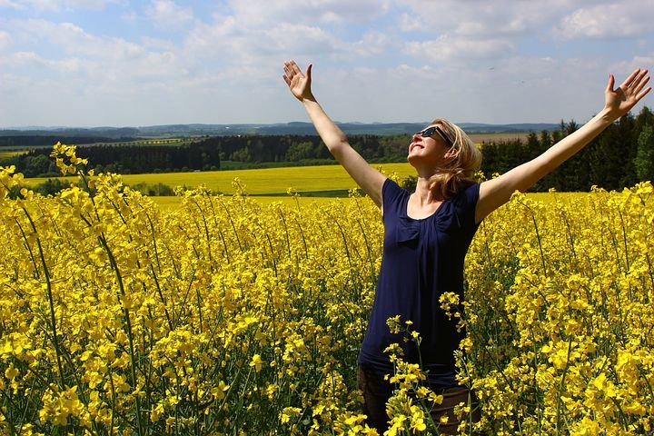 attitude adjustment, woman in blue dress with hands raised in worship standing in field of wildflowers