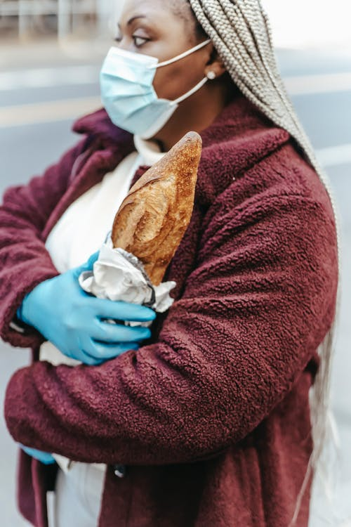 delusional fear, black woman carrying bread, wearing facemask and blue rubber gloves