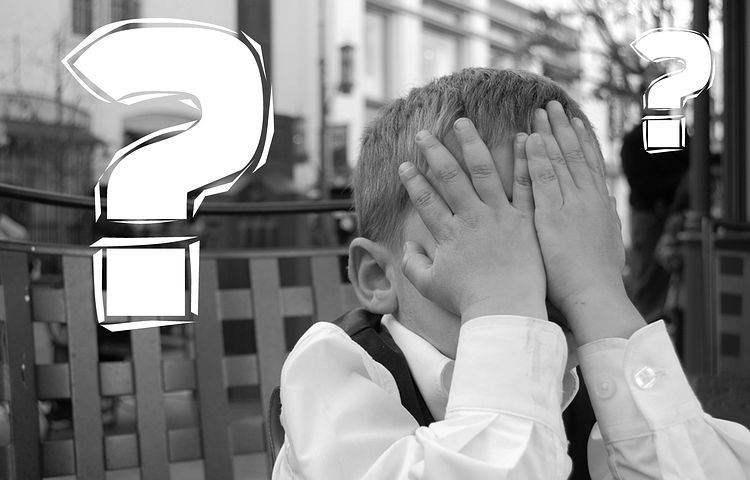 white question mark next to boy with hands covering face