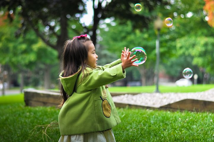 delusional fear, little girl in green jacket catching a bubble on the grass