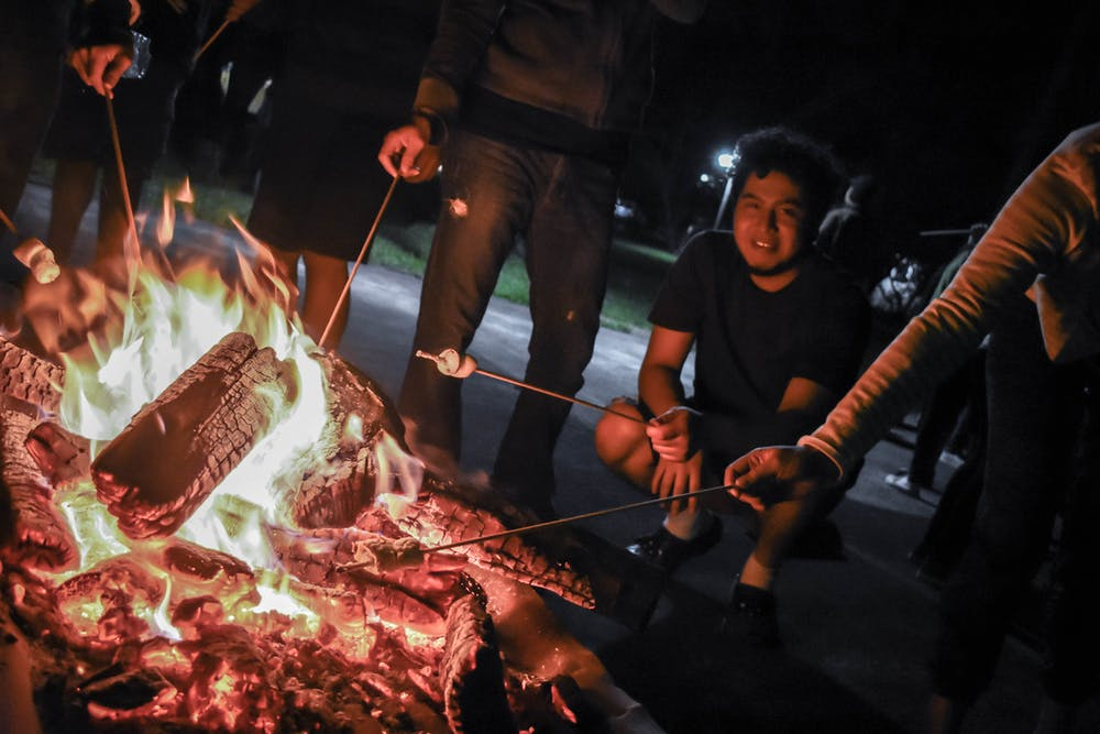 campfire, guy stooping to toast marshmallow over fire