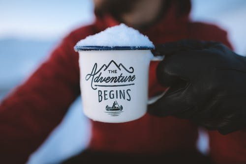snow in a mug, person in red hoodie holding mug