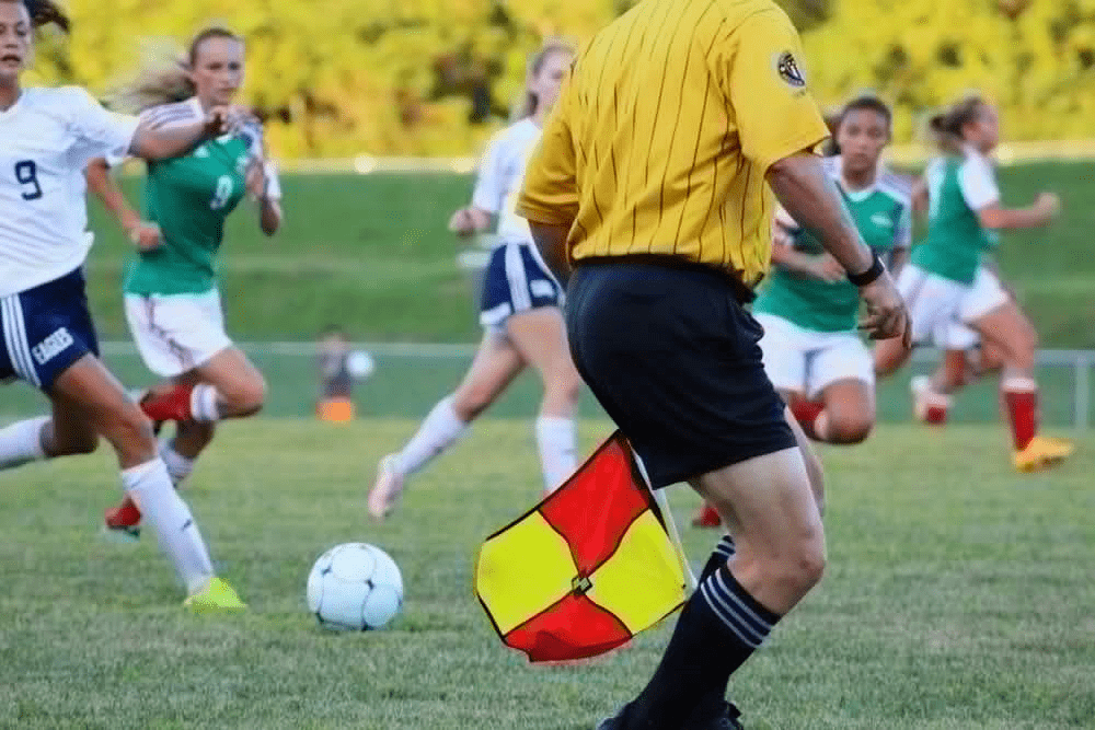 shoulders down view of soccer ref in yellow shirt, black shorts with yellow and red flag