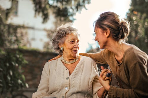 young woman holding older smiling older woman's hand