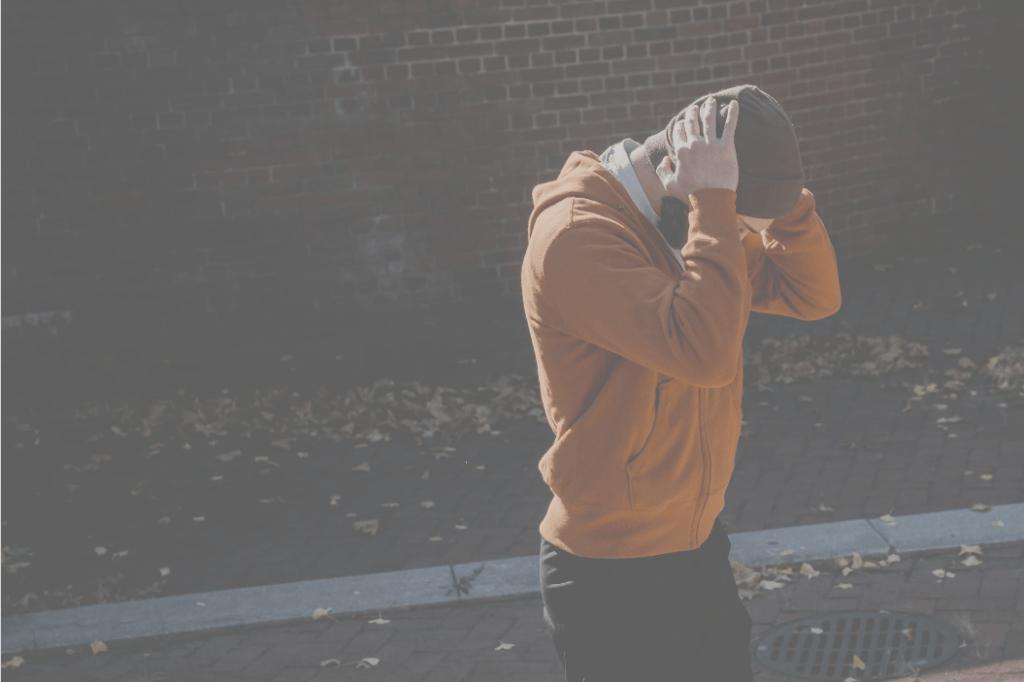 man in orange hoodie, black pants, knit cap, covering ears with hands