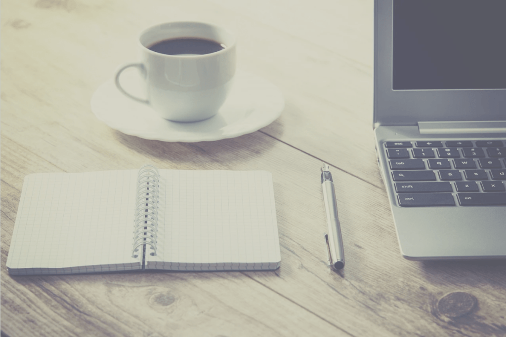 types of writing, coffee cup, pen, notepad, computer on table