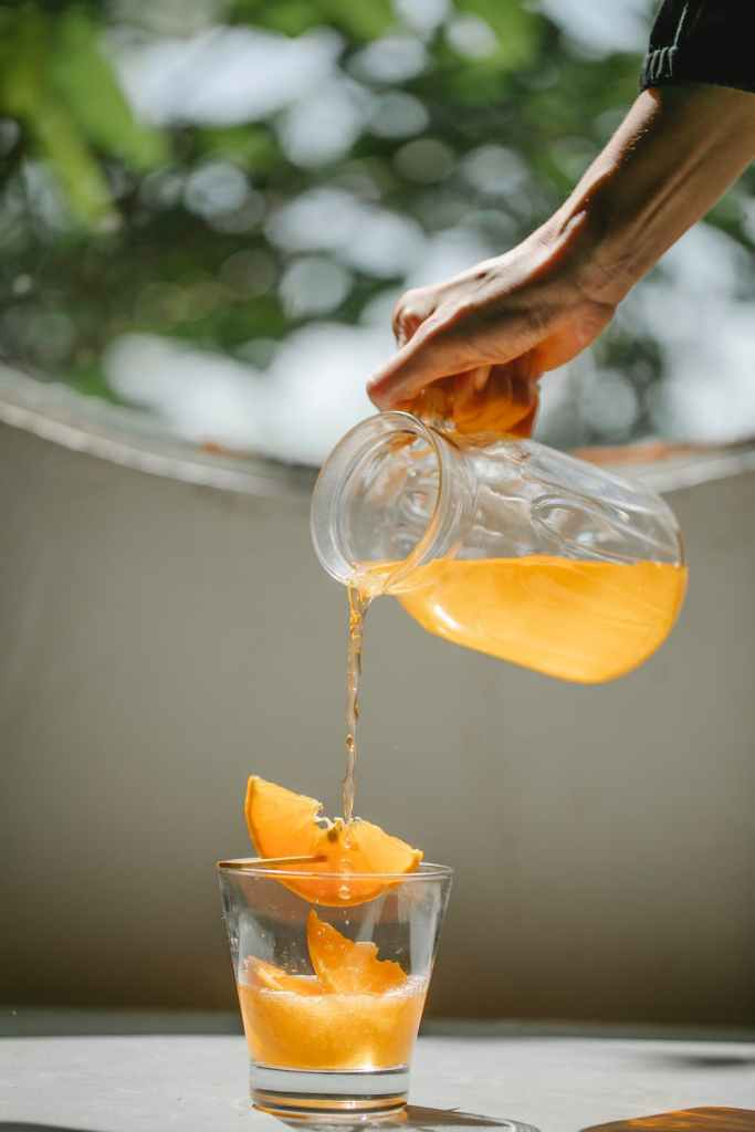 heatlh plan, hand pouring orange drink over glass with slices of orange in it