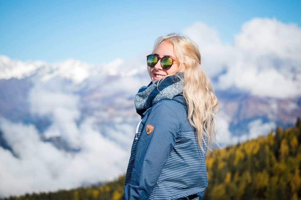 cognitive function, woman with blonde hair, sunglassed, blue coat, smiling outdoors