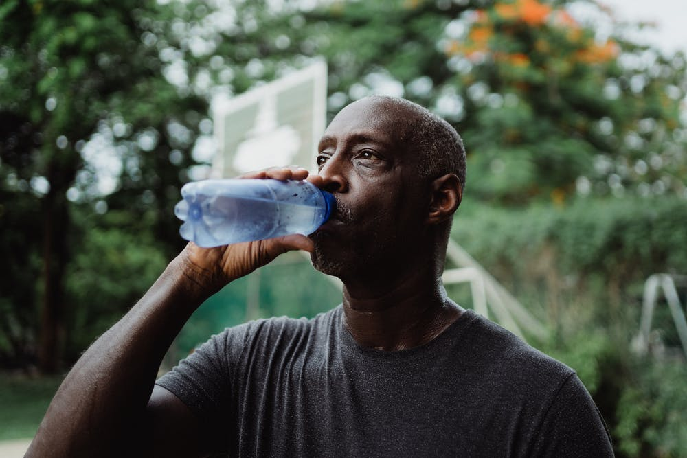 habits in life, man in gray tee shirt, drinking water from blue bottle