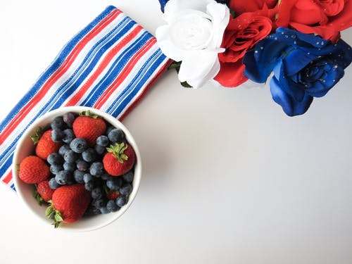 strawberries and blueberries in a bowl, red white and blue flowers and cloth