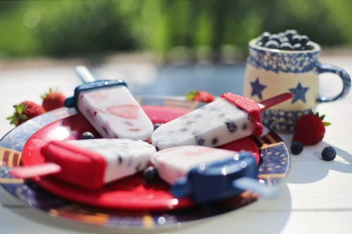 homemade popsicle recipes, plate of red, white and blue popsicles, small blue and white pitcher