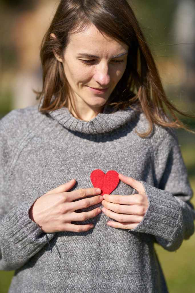 heart health, woman in gray sweater holding red paper heart to chest