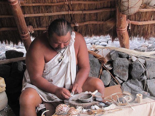native man wearing white cloth, leaning over bowl and plate