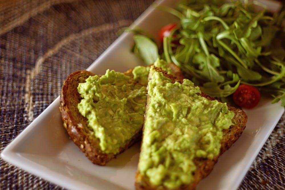 snack trends, avocado on toast, salad greens, white platter