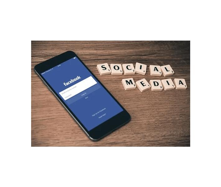 Social media influencer, cell phone, scrabble tiles spelling out social media