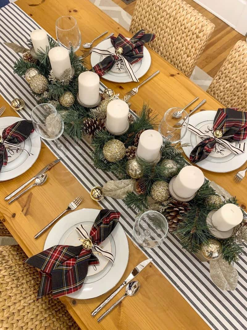 holiday table setting with candles, place settings, and table runner