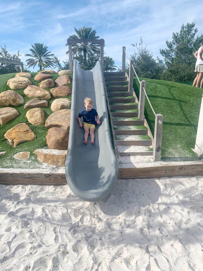 The Ultimate 30A Travel Guide for Families featured by top US travel blog, House of Navy: image of boy sliding down slide in Florida