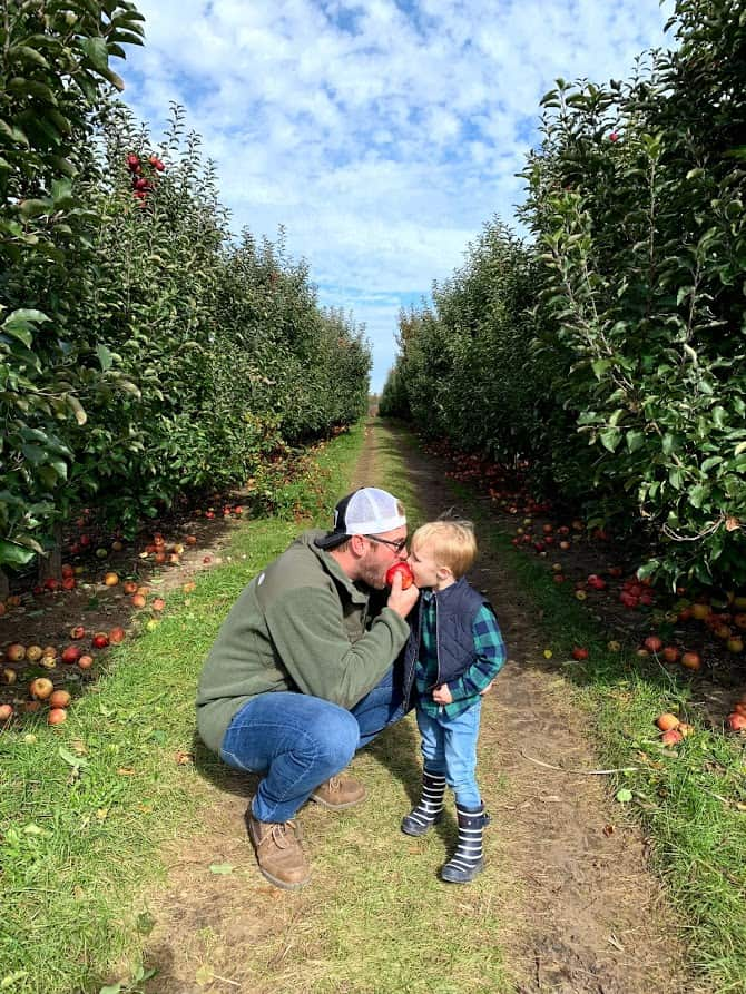 father in son in orchard with apple | Living in Michigan by popular Michigan lifestyle blog, The House of Navy: image of a father and his son eating an apple in an apple orchard in Rockford, MI.