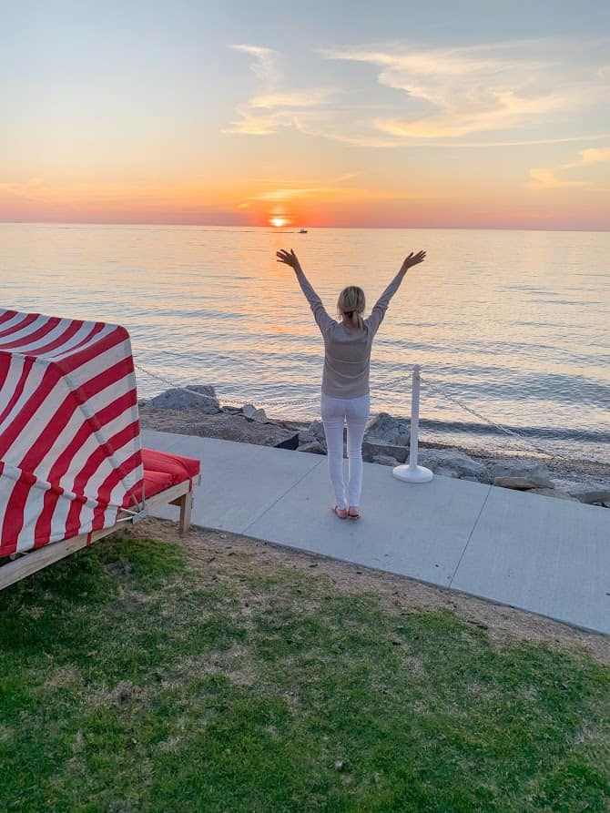 woman posing in front of sunset | Living in Michigan by popular Michigan lifestyle blog, The House of Navy: image of a woman standing in front of a lake in Petoskey, MI.