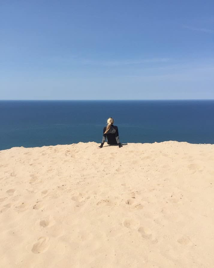 woman on sand dunes overlooking Lake Michigan | Living in Michigan by popular Michigan lifestyle blog, The House of Navy: image of a woman sitting in the sand at Sleeping Bear Dunes, MI.