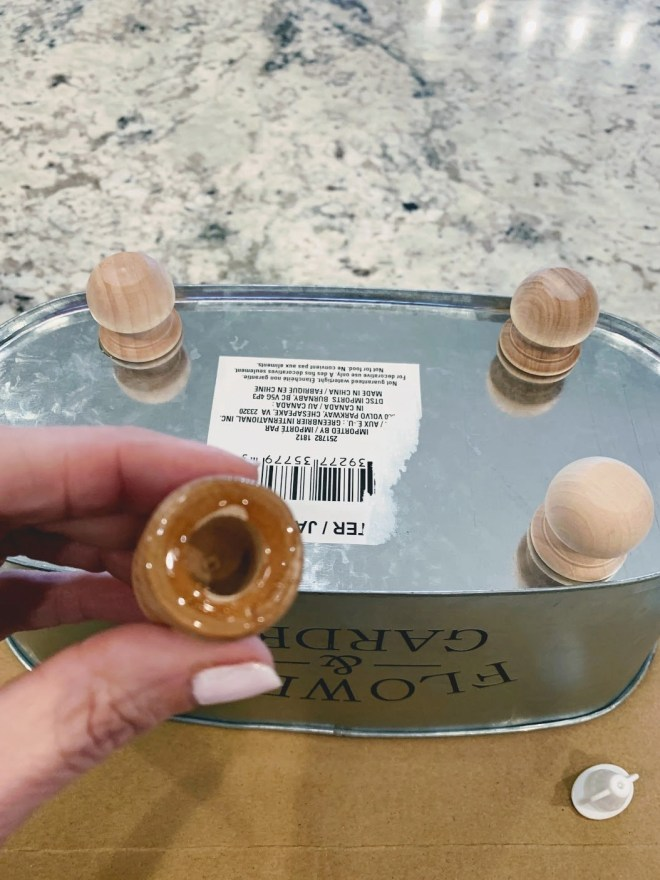 Glue the wood knobs onto the bottom of the DIY Farmhouse sink caddy with Gorilla Glue.