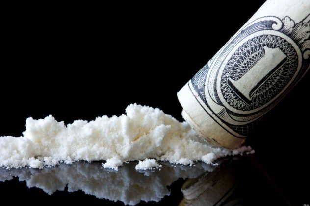Rolled-up dollar bill sliding across a mirror filled with cocaine symbolizing the need to hire a qualified Houston Criminal Lawyer