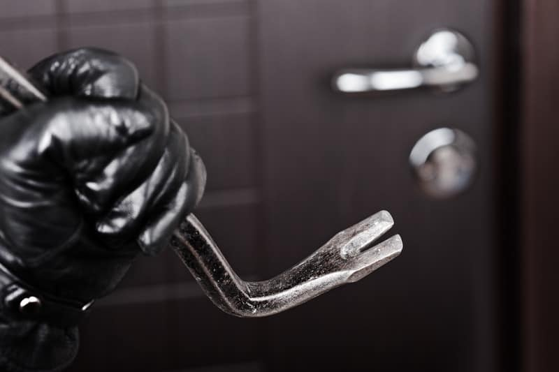 Black gloved hand with a crowbar in front of a locked door symbolizing the need to hire a qualified criminal lawyer