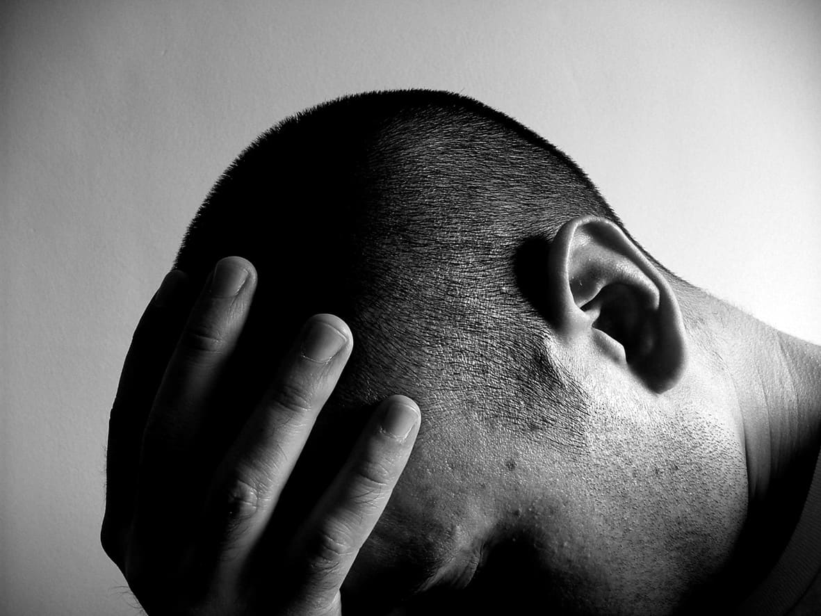 Male holding head down symbolizing need for a qualified Fort Bend Criminal Lawyer