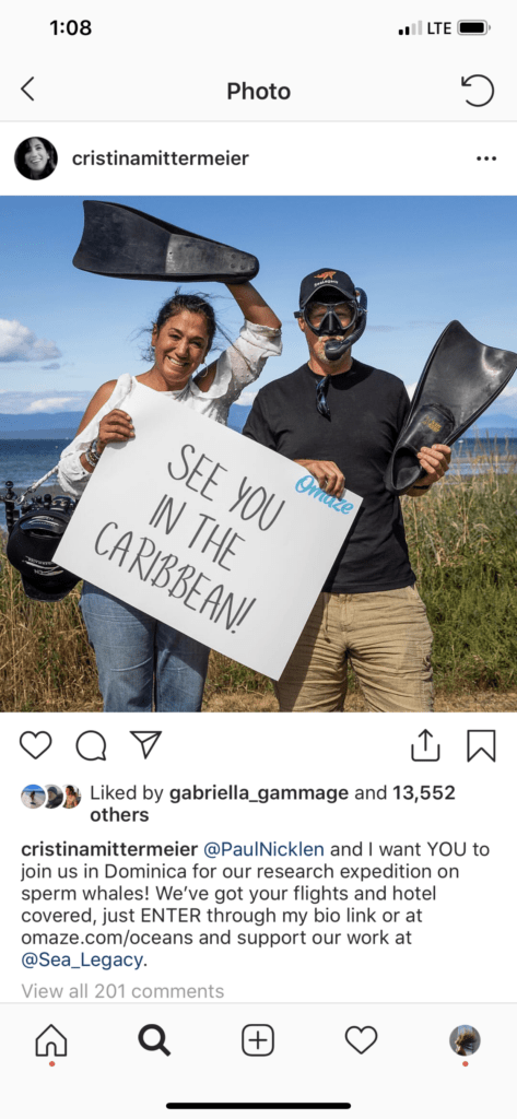 "Screenshot of Cristina and Paul Nicklen on Instagram holding a sign that says ""see you in the Caribbean!"
