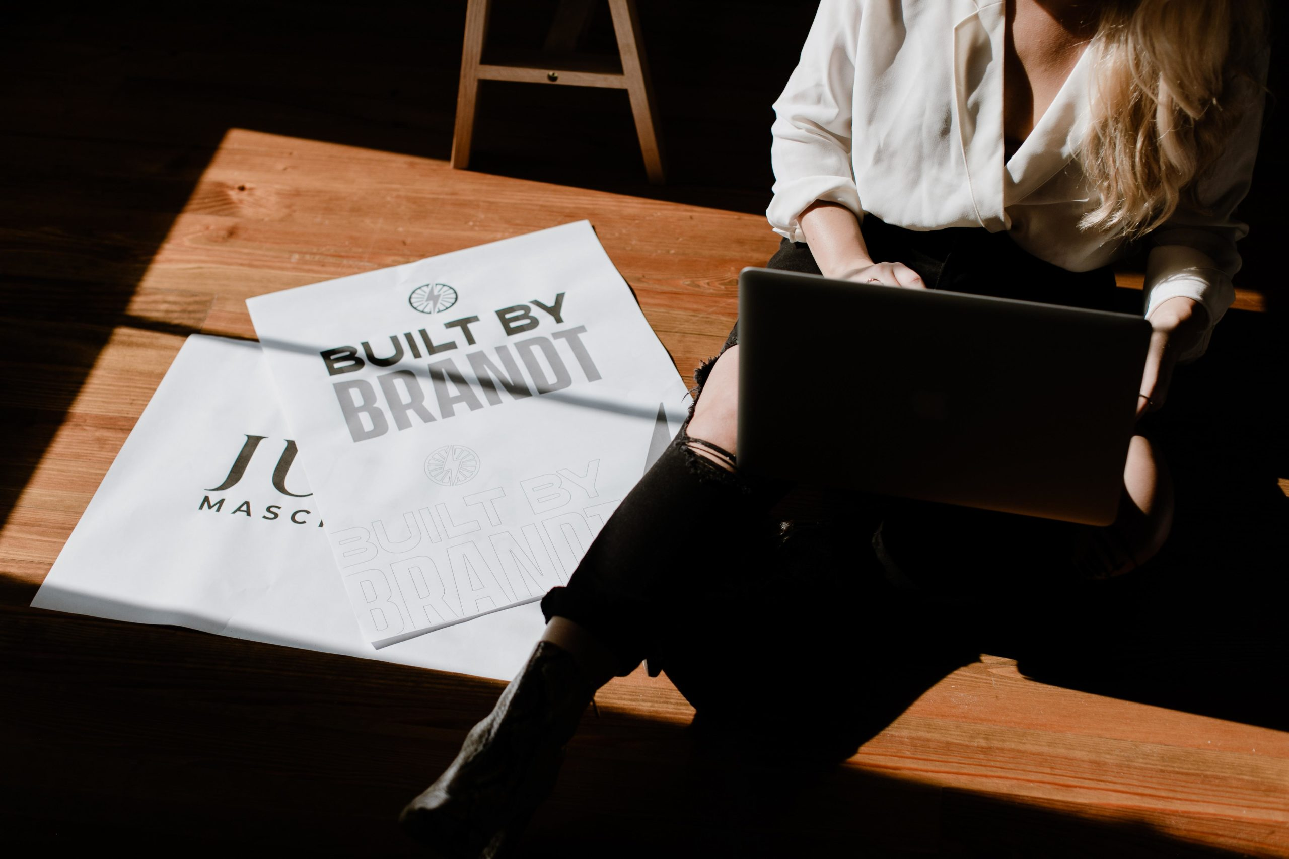 A woman is sitting on the floor with a laptop in her lap and papers scattered on the floor.