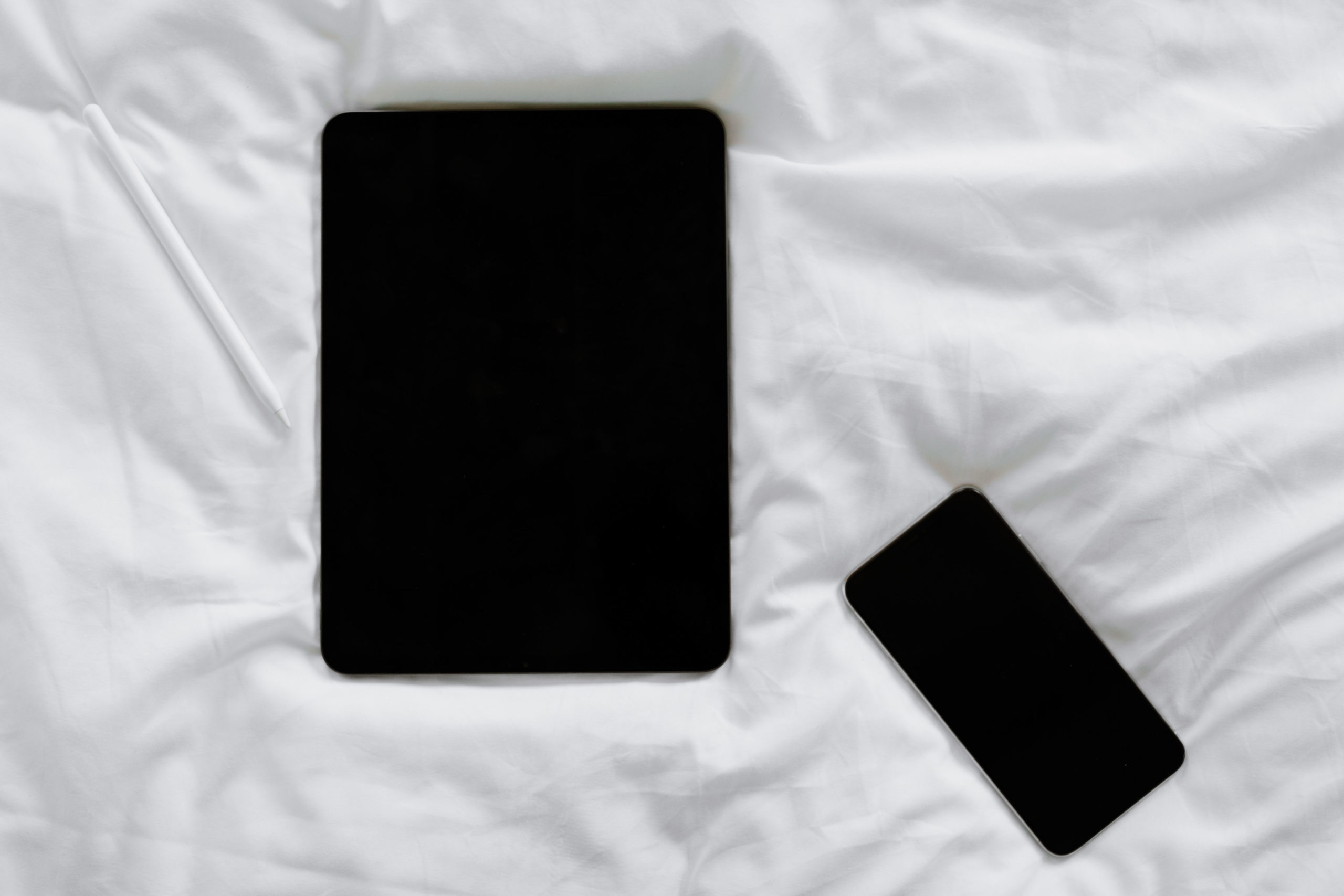 An iPad and iPhone laying on a white comforter.
