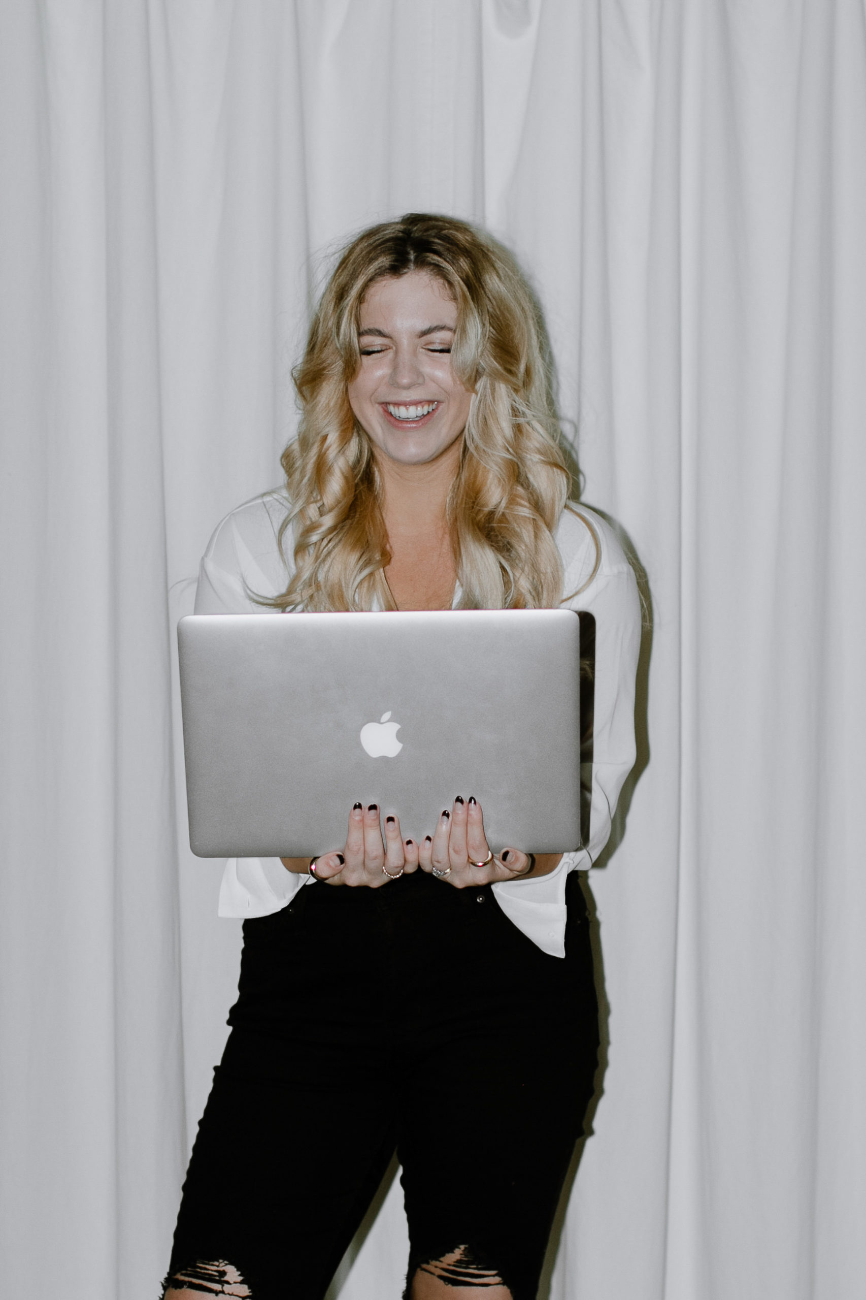 Photo of woman holding a laptop.